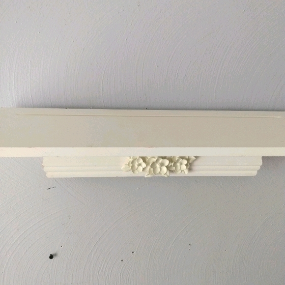 White washed wood white shelf with floral accents